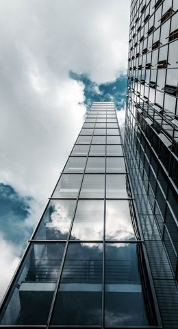 Tall glass building with an upward low angle view showing the design.